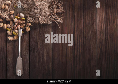 Pistachio nuts on an old spoon and composition from old wood and material. Top view and empty space on right side for your text - Stock Image