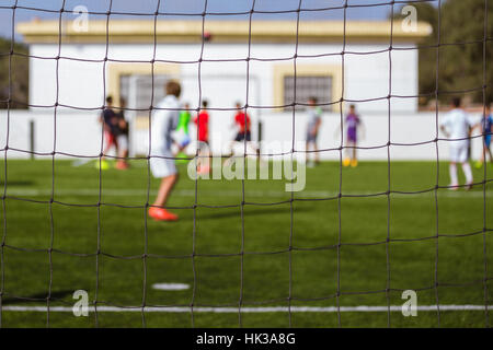 Kids playing soccer on a synthetic field, shot from the back - Stock Image