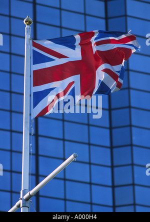 British flag waving in the wind against a backdrop of glass windows on Glasgow's Riverside - Stock Image