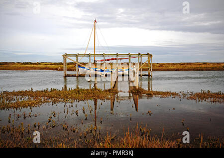 Access walkway and staging for boarding boats with moored yacht in Morston Creek at flood tide at Morston, Norfolk, England, United Kingdom, Europe. - Stock Image