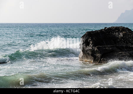 Scenic View Of Ionian Sea With Waves Splashing On Cliff Against Moody Sky - Stock Image