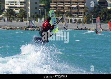 kiteboarder jumping over the white foam during a windy day  in front of the beach - Stock Image