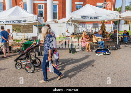 JONESBOROUGH, TN, USA-9/29/18:  Two musicians, play music at the Farmers' Market, while two women with a small child and an infant stroller walk by. - Stock Image