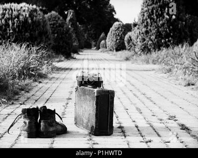 Leather boots, a vintage suitcase, and a film camera in its open leather case, in the middle of a brick road. A B/W photo. Grain noise added. - Stock Image