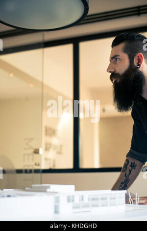 Architect in office, looking away in thought - Stock Image