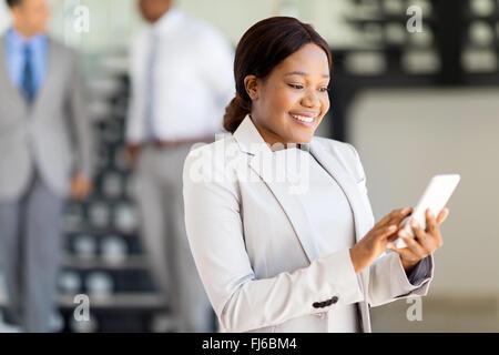beautiful African secretary using smart phone - Stock Image