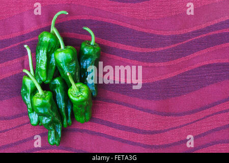 A small pile of seven mini green sweet chillies on a red wavy fabric background. - Stock Image