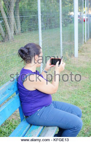 Woman sitting on a bench and taking a photo with her smartphone at a park in Poznan, Poland - Stock Image