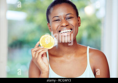 Ethnic girl holding an orange segment - Stock Image