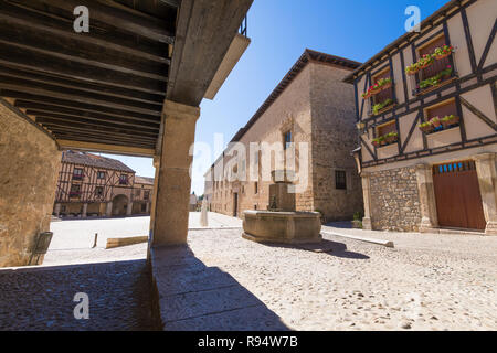 arcade of street with fountain in Penaranda de Duero village, with Palace of the Counts of Miranda, in Burgos, Castile and Leon, Spain, Europe - Stock Image