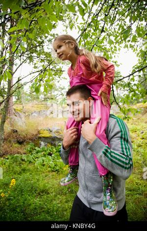 Girl sitting on man's shoulders, Swedish archipelago. - Stock Image
