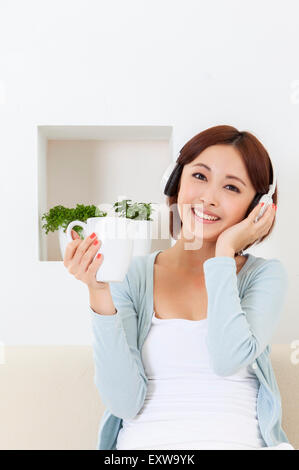 Young woman holding coffee cup and wearing headphone, - Stock Image