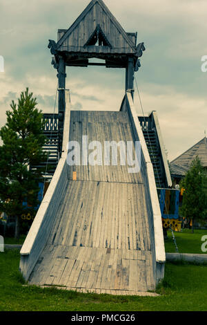Wooden slide for winter sledging with two stairs for lifting - Stock Image