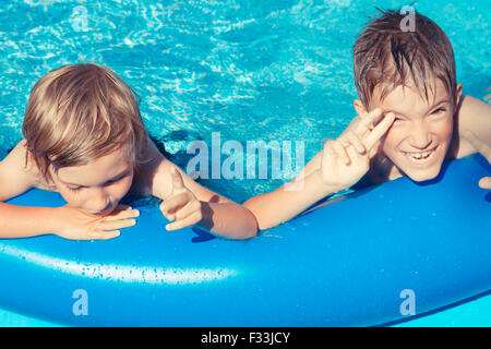 Two young boys outdoors playing in inflatable pool. - Stock Image