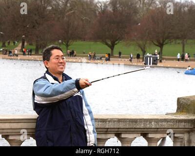 Oriental man taking selfie on the bridge at Hyde Park, London UK. - Stock Image