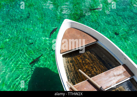 A small wooden boat in turquoise water in Lago Ghedina, an alpine lake in Cortina D'Ampezzo, Dolomites, Italy - Stock Image