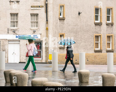 Holyrood, Edinburgh, Scotland, United Kingdom, 12th August 2018. UK Weather: the rain and mist as the remnants of Storm Debby hits the capital does not deter tourists at Holyrood Palace. Two women walking holding umbrellas - Stock Image
