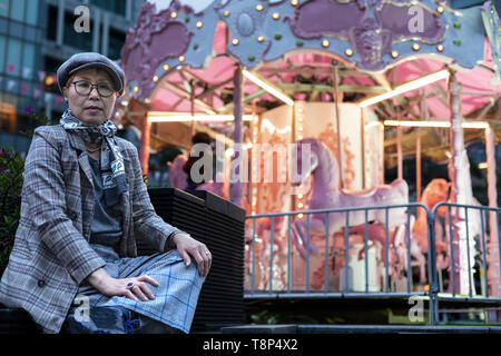 Fashionable Taiwanese woman of Chinese ethnicity sitting down with merry-go-round in the background - Stock Image