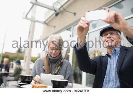 Senior couple using digital tablet and camera phone, drinking coffee at sidewalk cafe - Stock Image