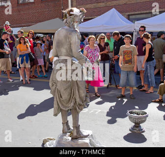 ASHEVILLE, NORTH CAROLINA, USA – 9/5/2010: An amazing and popular human statue, a busker known as the Silver Drummer Girl, entertains crowds in the st - Stock Image