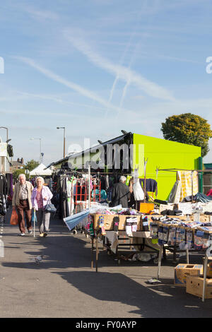 Outdoor stalls mostly selling clothing on Bolton market. A few people are browsing - Stock Image