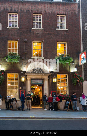 Early evening, customers drinking outside the Henry Holland Pub in London, UK, Europe. - Stock Image