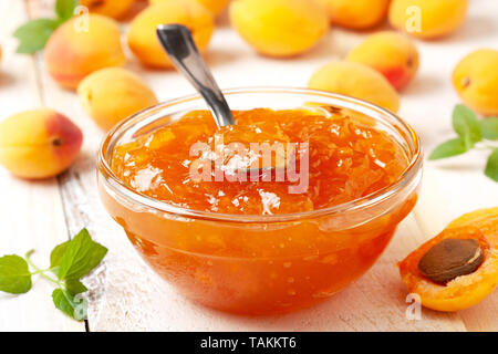 apricot jam in a glass bowl, fresh apricots on a wooden background close-up - Stock Image