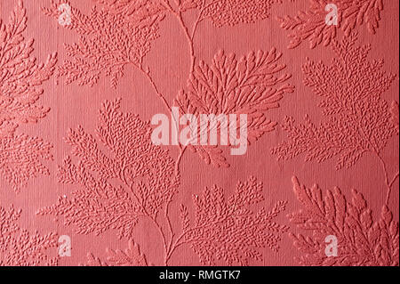 Textured wallpaper showing the texture and pattern in red - Stock Image
