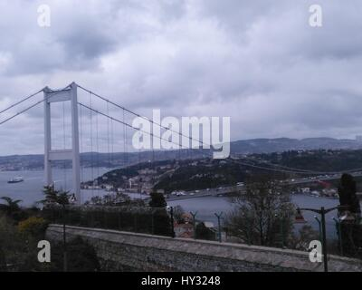 View Of Suspension Bridge Against Cloudy Sky - Stock Image