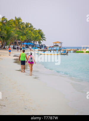 A male female couple walking hand in hand on West Bay Beach in Roatan Honduras. - Stock Image
