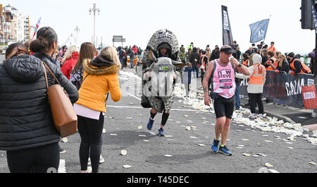 Brighton UK 14th April 2019 -   A Save the Rhino campaigner with Thousands of runners some in fancy dress take part in this years Brighton Marathon which is celebrating its 10th anniversary Credit: Simon Dack/Alamy Live News - Stock Image