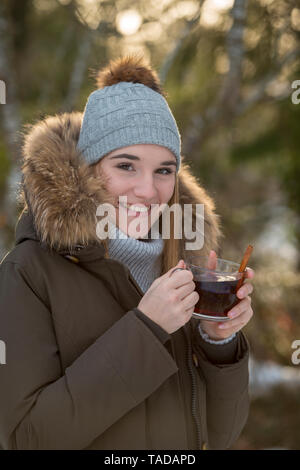 Portrait of smiling young woman drinking tea in winter - Stock Image