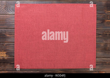red cloth napkin on dark rustic wooden background top view with copy space. - Stock Image