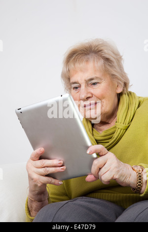 Senior lady looking at a digital tablet (unbranded i-pad) - Stock Image