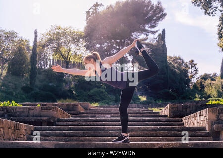 beautiful young girl doing yoga exercise on the stairs of the park, morning workout outdoors, sports and healthy lifestyle - Stock Image