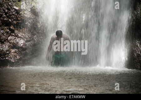 Dark View Falls, a man standing under the waterfall with dramatic light - Stock Image