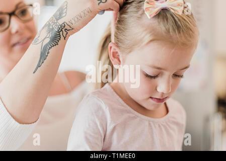 Mother with tattoos fixing daughterÕs hair - Stock Image