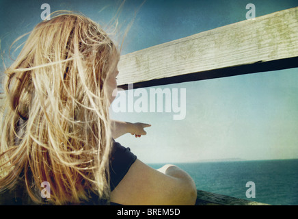 girl pointing out to sea - Stock Image