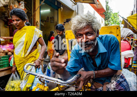 A man in a street market in George Town, Chennai, India pushes his bicycle amongst the stalls - Stock Image
