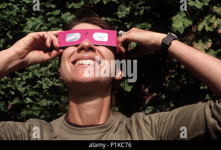 woman enjoying the viewing of the solar eclipse wearing protective eye glasses - Stock Image