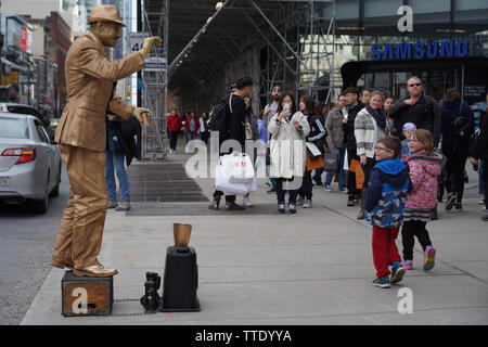 street artist living statue waving at kids passing by outside in a north american city - Stock Image