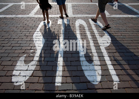 Three people walk across a brick street in the early evening in downtown Rogers, Arkansas, U.S.A. - Stock Image
