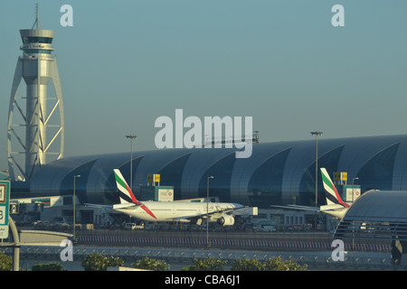 Emirates aircraft and control tower at Dubai Airport, DXB, United Arab Emirates - Stock Image