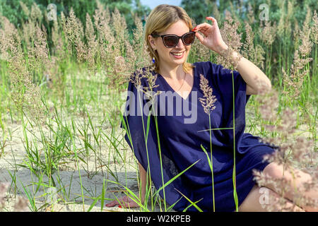 beautiful blonde woman in blue dress and sunglasses posing while sitting on ground among grass at summer meadow, holding her eyeglasses and looking wi - Stock Image