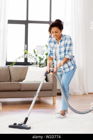 woman or housewife with vacuum cleaner at home - Stock Image
