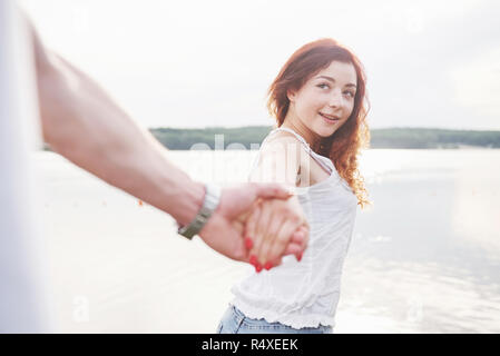 A smiling happy woman with a playful expression and a hand with her husband. - Stock Image