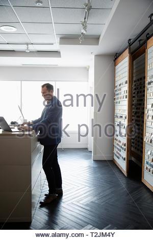 Male interior designer using laptop in design studio - Stock Image