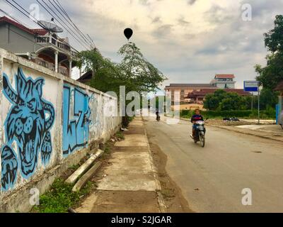 Locals on scooters in Vang Vieng road Laos - Stock Image