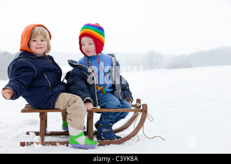 Two boys on a sledge in the snow - Stock Image