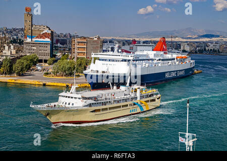 Anes Lines Agios Nektarios passing Hellenic Seaways car and passenger ferry Hellenic Samos moored in port of Piraeus Athens Greece Europe - Stock Image
